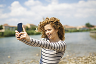 Italy, Verona, portrait of smiling woman taking selfie with smartphone at riverside - GIOF001040