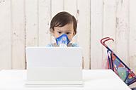 Girl using inhaler looking at digital tablet - DRF001711