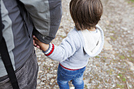 Father and son hand in hand outdoors - VABF000487