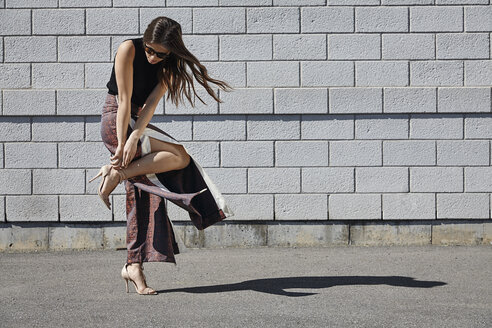 Fashionable young woman in front of brick wall adjusting her shoe - MHCF000019