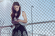 Attractive young woman at a fence texting on cell phone - MHCF000025