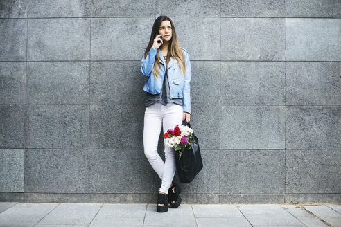 Young woman on cell phone with bunch of flowers in her bag - EBSF001362