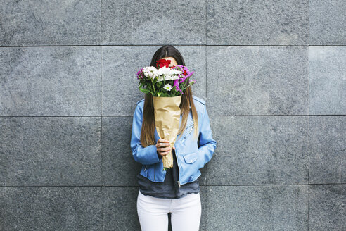 Young woman holding bunch of flowers in front of her face - EBSF001365