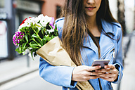 Young woman holding cell phone and bunch of flowers - EBSF001371