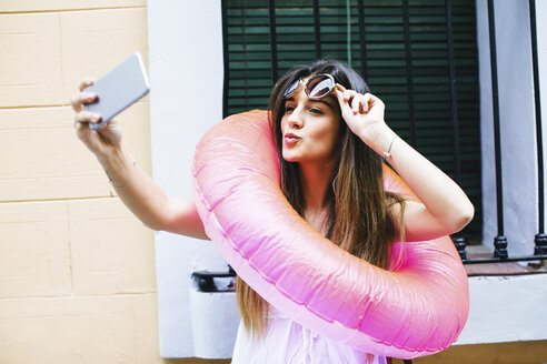 Young woman with bathing ring around the neck taking a selfie - EBSF001374