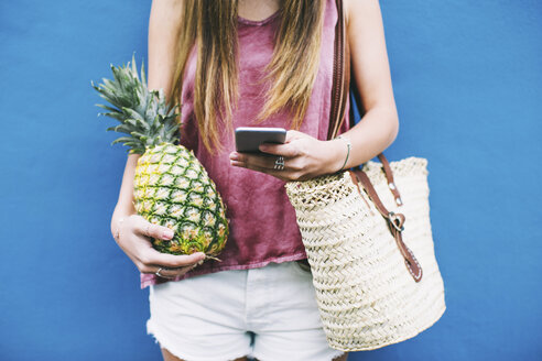 Young woman standing with beach bag, cell phone and pineapple - EBSF001377