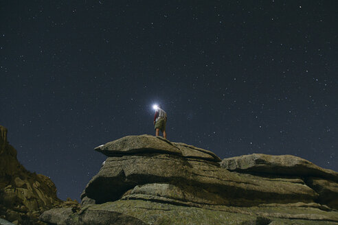 Spain, man with headlamp under a starry sky on a rock in La Pedriza - ABZF000532