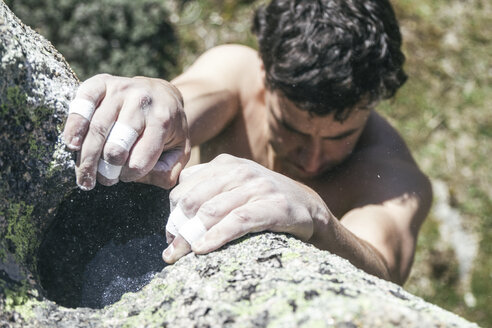 Hands of a climber with sticking plaster and chalk during a boulder climbing - ABZF000547