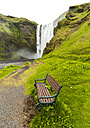 Iceland, empty bench, waterfall in the background - JLRF000025