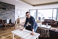Man standing in living room, leaning on desk - HAPF000400