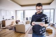 Man standing in living room, using digital tablet - HAPF000415