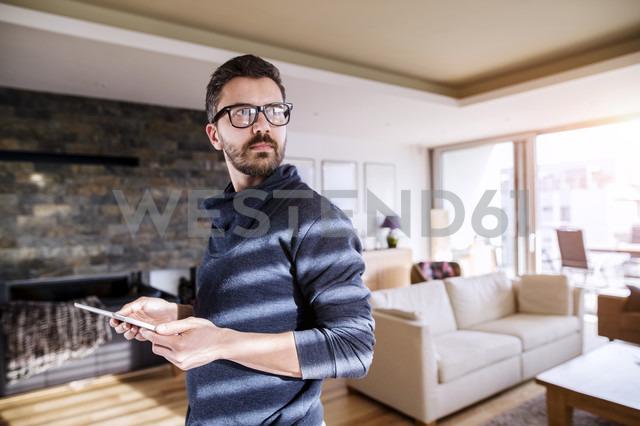 Man standing in living room, using digital tablet - HAPF000418 - HalfPoint/Westend61