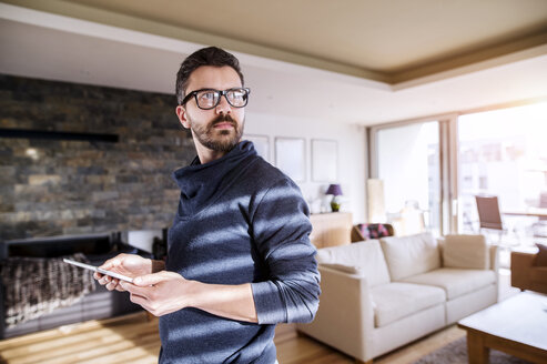 Man standing in living room, using digital tablet - HAPF000418