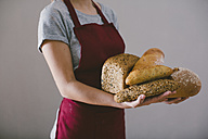 Woman holding different home made breads - EBSF001397