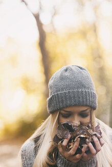 Teenage girl smelling autumn leaves - SELF000092