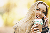 Smiling teenage girl on cell phone holding disposable cup - SELF000098
