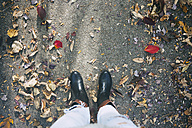 Teenage girl standing on path with autumn leaves - SELF000104
