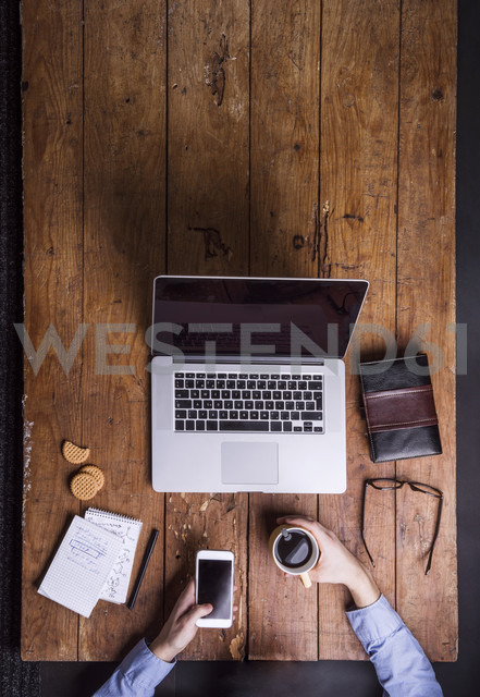 Man with coffee cup and smartphone at his desk - HAPF000446