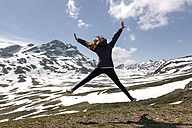Spain, Asturias, Somiedo, playful woman jumping in mountains - MGOF001860