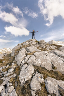 Spain, Asturias, Somiedo, man standing with outstretched arms in mountains - MGOF001872