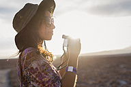 Chile, San Pedro de Atacama, woman with camera in the desert in backlight - MAUF000612