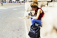 Italy, Verona, woman sitting on stairs looking at camera - GIOF001057