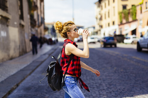 Italy, Verona, woman drinking coffee to go in the city - GIOF001063