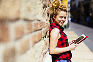 Smiling woman leaning against a brick wall holding digital tablet - GIOF001066