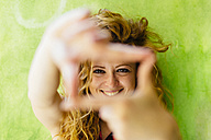 Portrait of smiling woman shaping a finger frame - GIOF001075