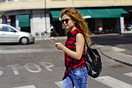 Italy, Verona, woman crossing street looking at cell phone - GIOF001084