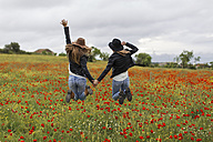 Two woman jumping, poppy field, holding hand - JPF000156
