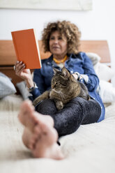 Woman with cat on bed reading book - MAUF000639