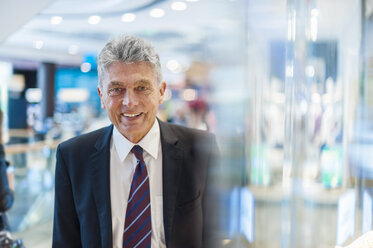 Portrait of smiling senior man at shop window - DIGF000536