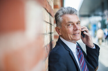 Senior businessman leaning against brick wall talking on cell phone - DIGF000539