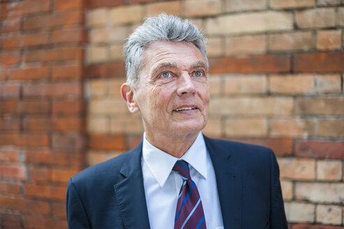Senior businessman at brick wall looking up - DIGF000542