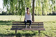 Portrait of young woman sitting on backrest of park bench - GIOF001092