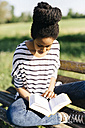Young woman sitting on park bench reading a book - GIOF001095