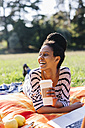 Happy woman with coffee to go lying on blanket on a meadow - GIOF001110