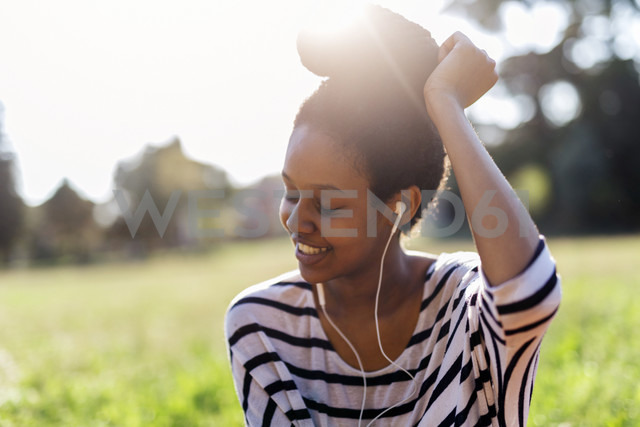 Smiling woman hearing music with earphones - GIOF001119