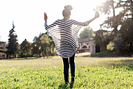 Woman dancing on a meadow while hearing music with earphones - GIOF001122