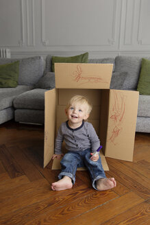 Smiling toddler sitting in a cardboard box at home - LITF000319