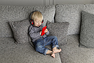 Toddler sitting on couch listening music with headphones and smartphone - LITF000325