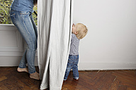Toddler playing peek-a-boo behind the curtain with his mother - LITF000331
