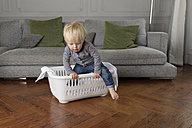 Toddler getting out of a laundry basket - LITF000334