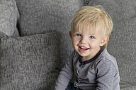 Portrait of smiling blond toddler sitting on couch - LITF000340
