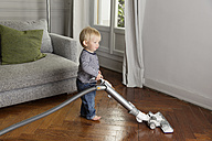 Toddler vacuuming a wooden floor in the living room - LITF000343
