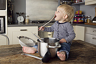 Toddler sitting on the kitchen table playing with kitchen utensils - LITF000346