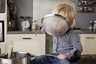 Portrait of toddler boy sitting on the kitchen table playing with strainer - LITF000349