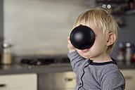 Toddler boy hiding his face behind a ladle - LITF000352