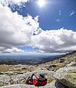 Spain, Sierra de Gredos, hiker sitting in mountainscape - LAF001645